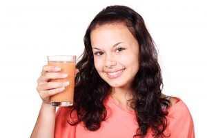 Beautiful smiling girl holding a glass of juice