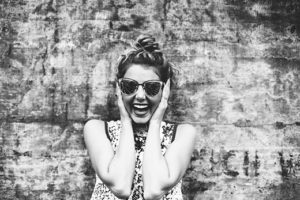 Smiling woman with sunglasses clicking picture