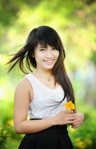 Beautiful smiling girl holding flower